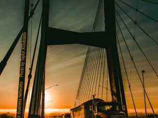 Trucks Crossing a Bridge at Sunset